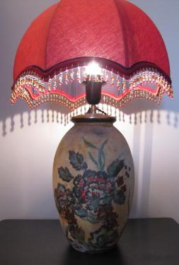 Réalisée à partir d'un vase ancien peint à la main, cette jolie lampe d'ambiance est associée à un abat-jour dôme confectionné en lin au ton rouge oriental et doublé d'un voile de coton marine.Il est agrémenté de finitions, soutache, galon et perles reprenanr les mêmes couleurs.