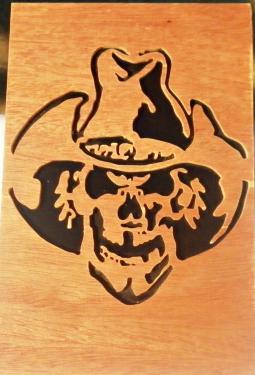 tableau de 20 cm x 30 cm représentant une tête de mort portant un chapeau de cow-boy. Entièrement réalisé à la main à la scie a chantourner dans mon atelier.