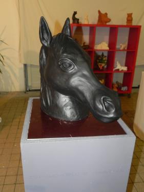 sculpture d'une tête de cheval en terre cuite, puis peinte en noir elle fait 40cm de haut pour 47cm de large