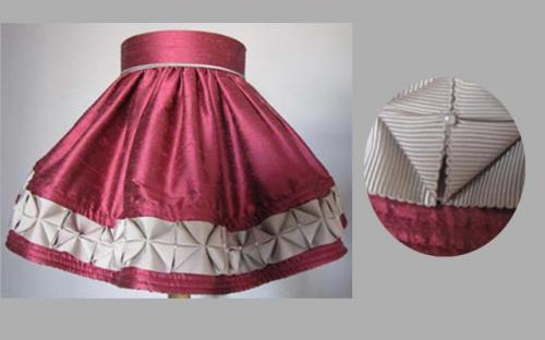 Réalisé en soie de couleur rose et doublé d'une mousseline de soie rose également,ce modèle est passepoilé et agrémenté d'un ruché ton gris orné d'une délicate perle.