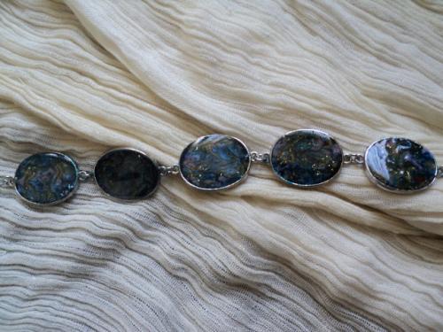 Pierre de lune:Bracelet en métal argenté, composé de cinq médaillons reliés entre eux par deux anneaux et décorés par des peintures fantaisie, dans les tons bleus principalement et quelques touches de doré et de rouge. Pas un médaillon ne ressemble à l'autre. Le tout est enfermé dans une coquille de résine. Le bracelet se ferme grâce à une chaînette de plusieurs anneaux et d'un fermoir mousqueton. Le bracelet s'adapte à toutes les tailles de poignet